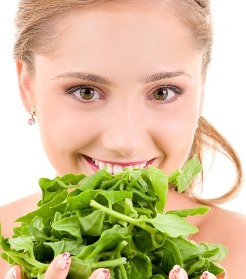 smiling women eats spinach