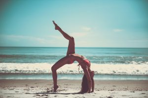 Woman doing pose that requires flexibility on the beach